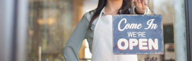 Young woman holding open sign up outside of a home goods downtown store front. Photograph taken in downtown Grand Rapids, Michigan.